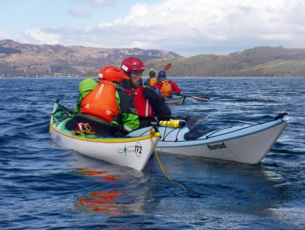 Rafted sea kayak tow - checking vital signs on the move