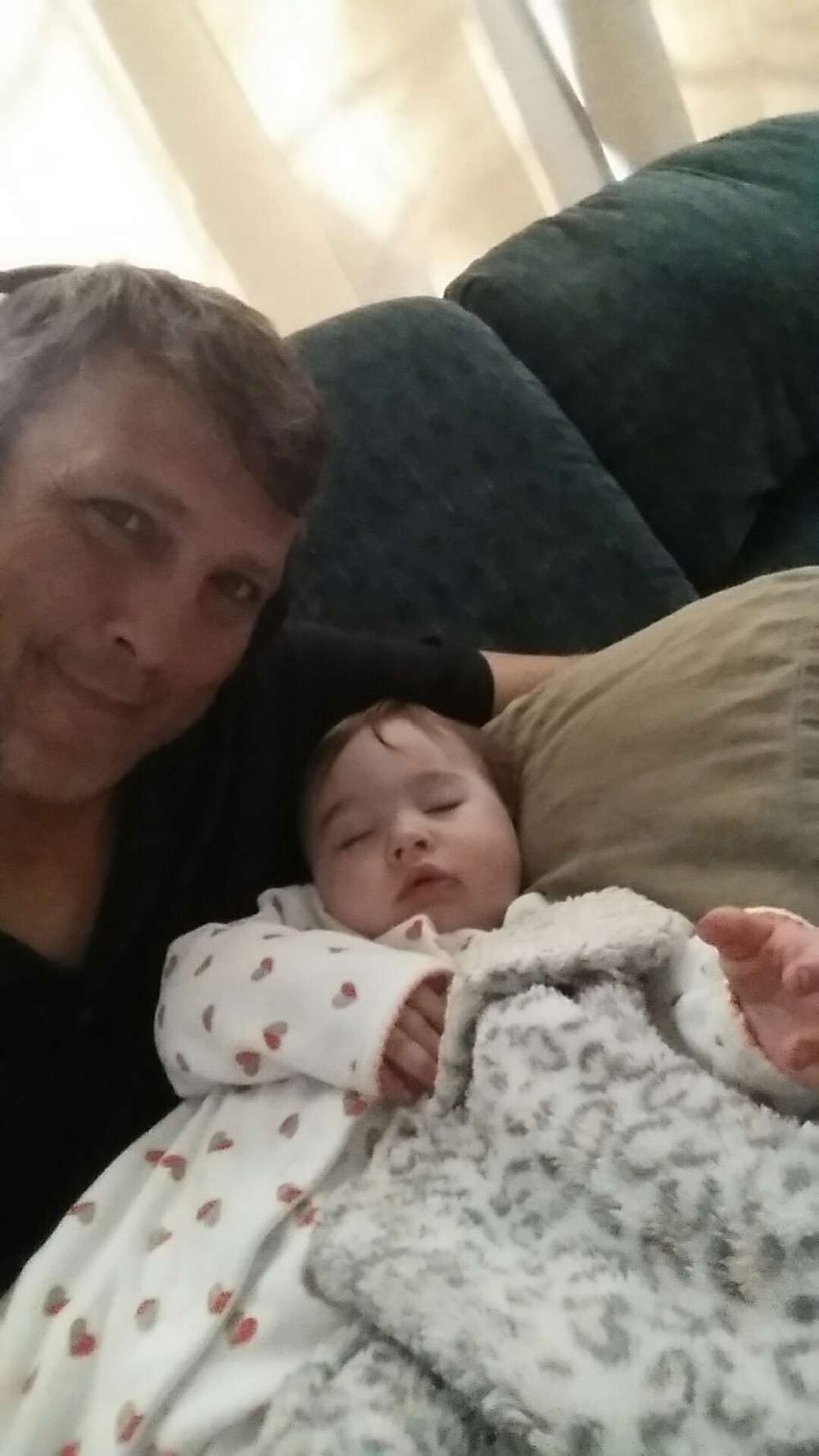 Dad holding sleeping baby on a pillow.