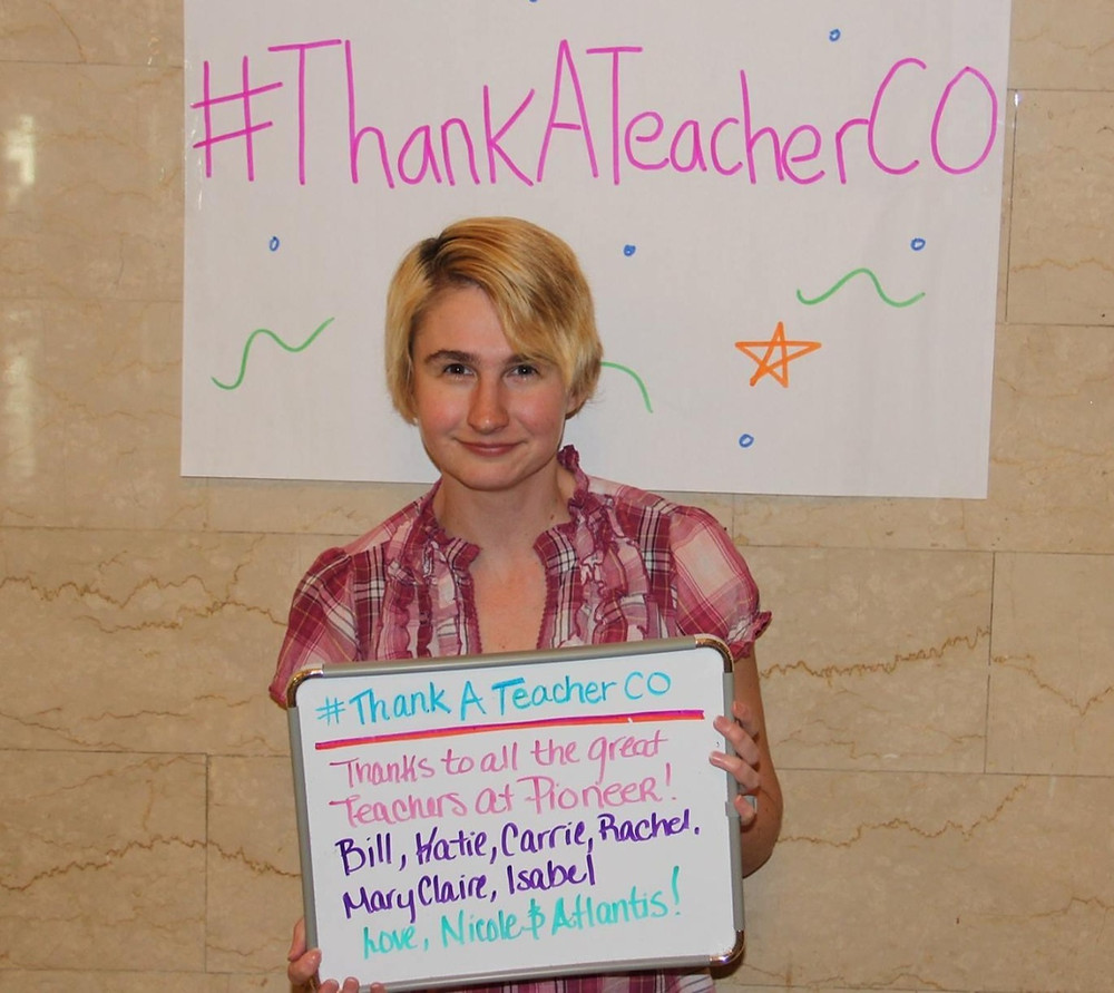 Picture of woman standing in front of sign that reads #ThankATeacherCO