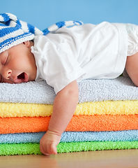 Yawning sleeping baby on colorful towels