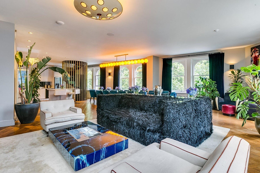 The private apartment of the Laylow club in Notting Hill with a huge furry navy blue sofa and a long dining table in the background