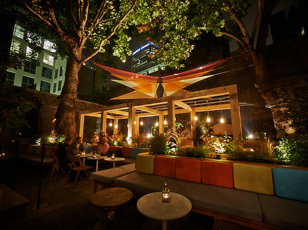 The garden of a member's club in central london, lit with festoon lights and candles