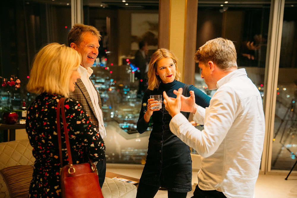 People talking and laughing at a drinks party in the suite of the shangri-la hotel at the shard in London