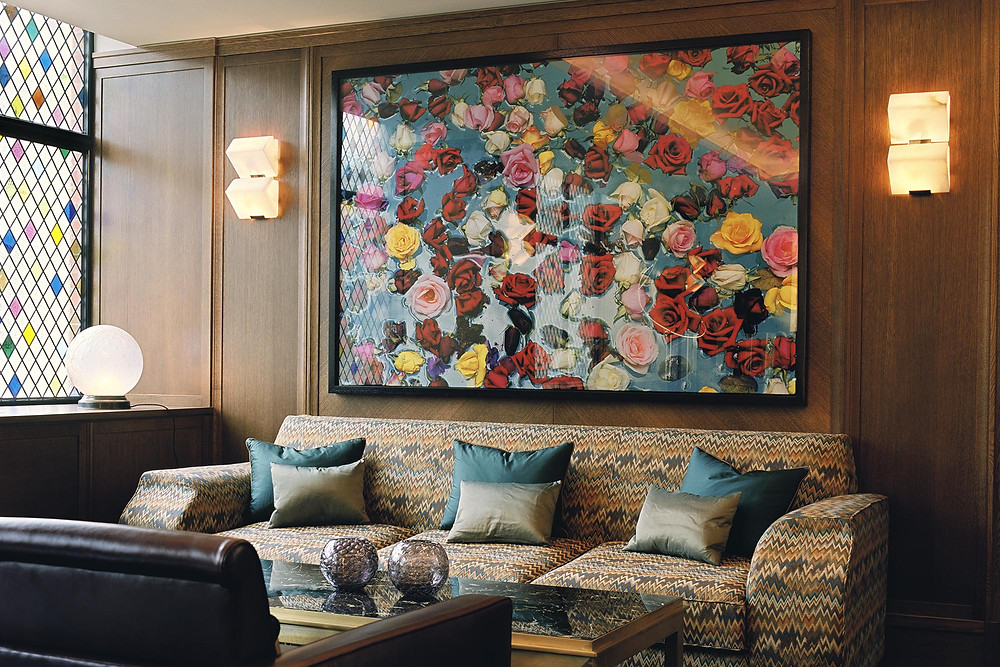 Drawing room at the club above the Ivy restaurant with stained glass windows, a large piece of artwork with roses on and a plush comfortable sofa