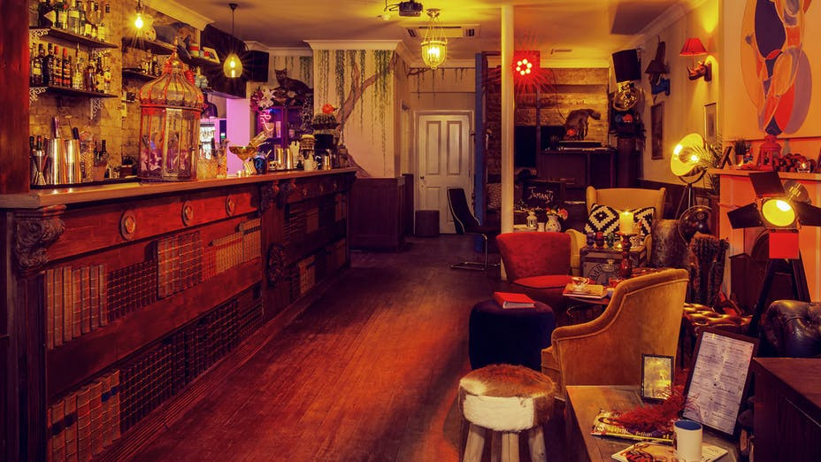 An orange and red lit bar in a small venue in Fulham London