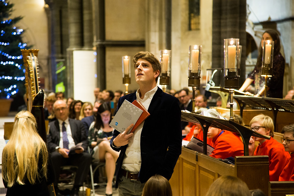 freddie hutchins performs in a cathedral lit by candles
