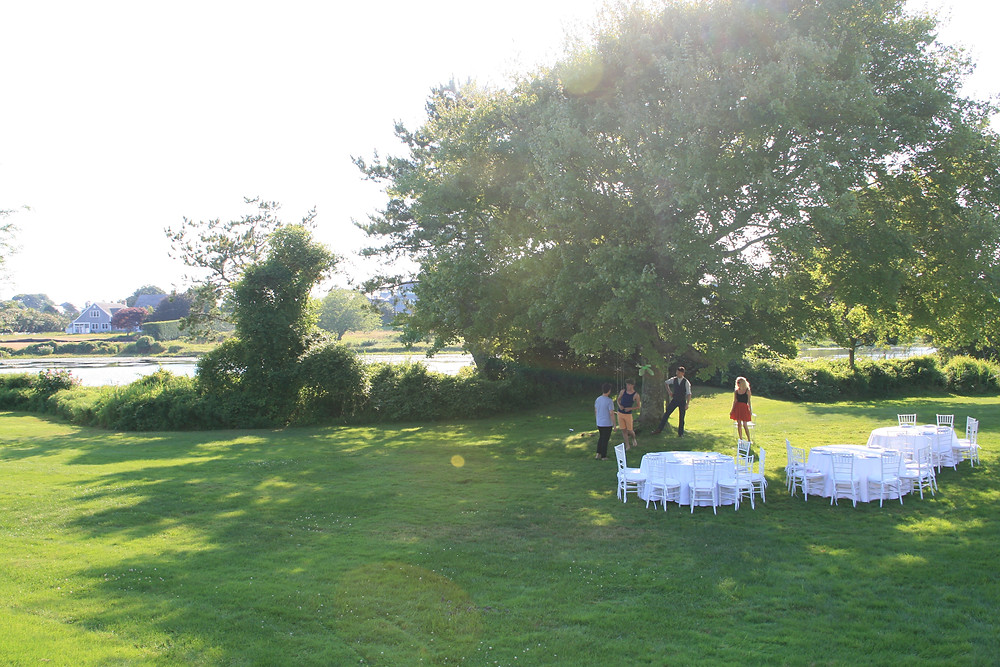 actors in a vast garden by a lakeside in the hamptons rehearsing for a play to be performed in front of 3 white tables