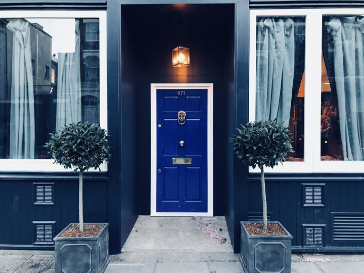 A bright blue front door, sandwiched between 2 large windows