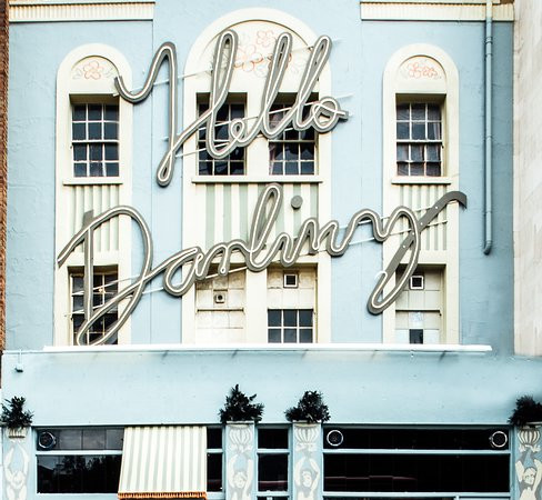 The outside of Hello Darling, a restaurant in Waterloo with 1950s style retro typeface in front of a blue exterior