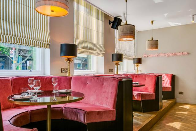 Bright pink velvet booth seats in the Laylow Club in Notting Hill