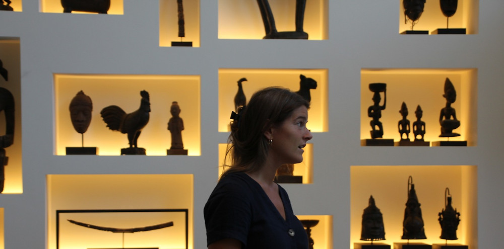 Actress Ellie Ross rehearses in front of an elegant wall of African statues