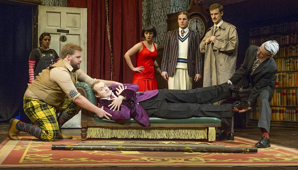 The Play that Goes Wrong original cast in the middle of a scene where 2 characters are trying to lift a dead body off from a sofa
