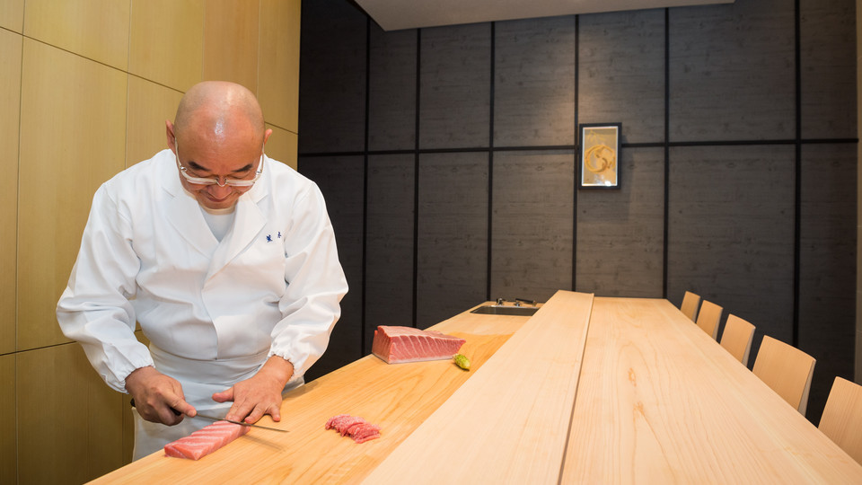 Mitsuhiro Araki famous sushi chef slicing raw fish while seats sit empty at his restaurant