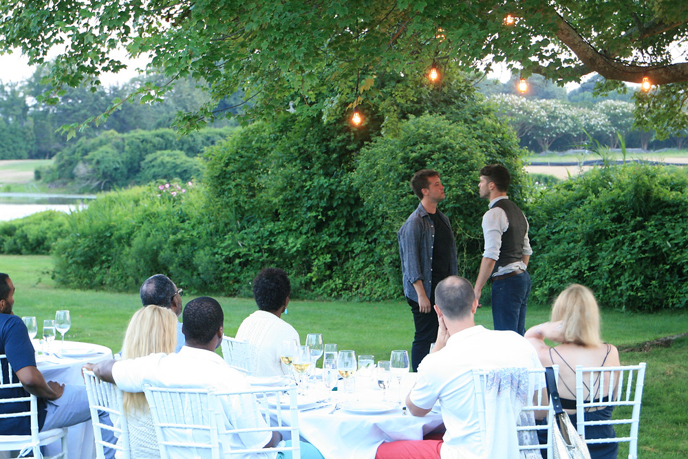 a group of wealthy people watch on as 2 actors perform shakespeare in front of their dinner tables in the garden