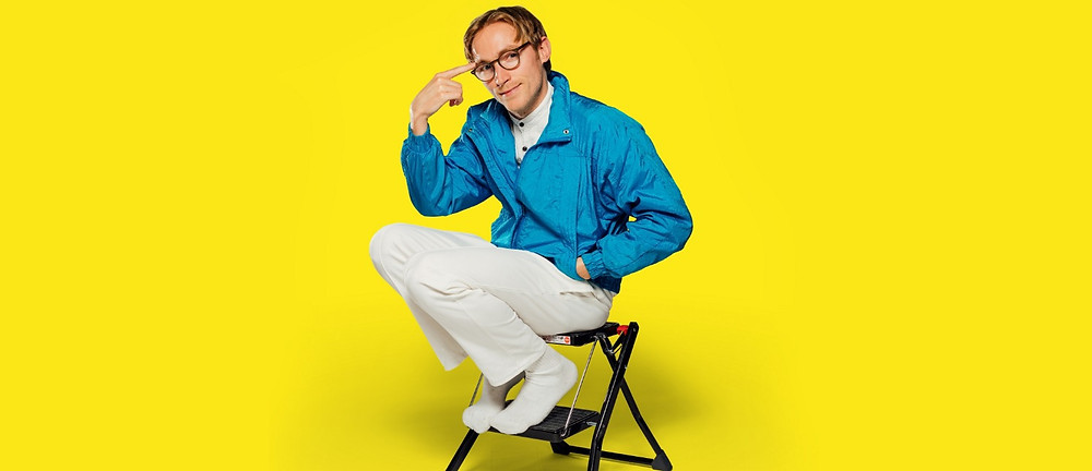 geeky literary comic character sat on a footstep in front of bright yellow background