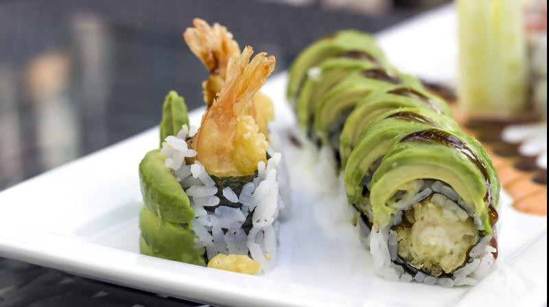 sushi up close perfectly arranged with prawn tails sticking out and rings of green avocado