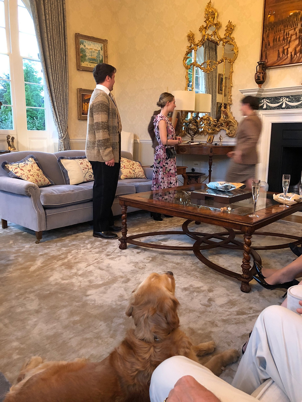 Actors perform Noel Coward in a drawing room with elegant gold mirror and a dog watches on