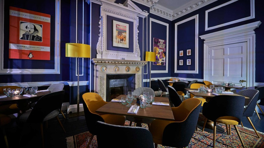 A restaurant with blue walls and a large Shakespeare picture on the wall with all the chairs empty