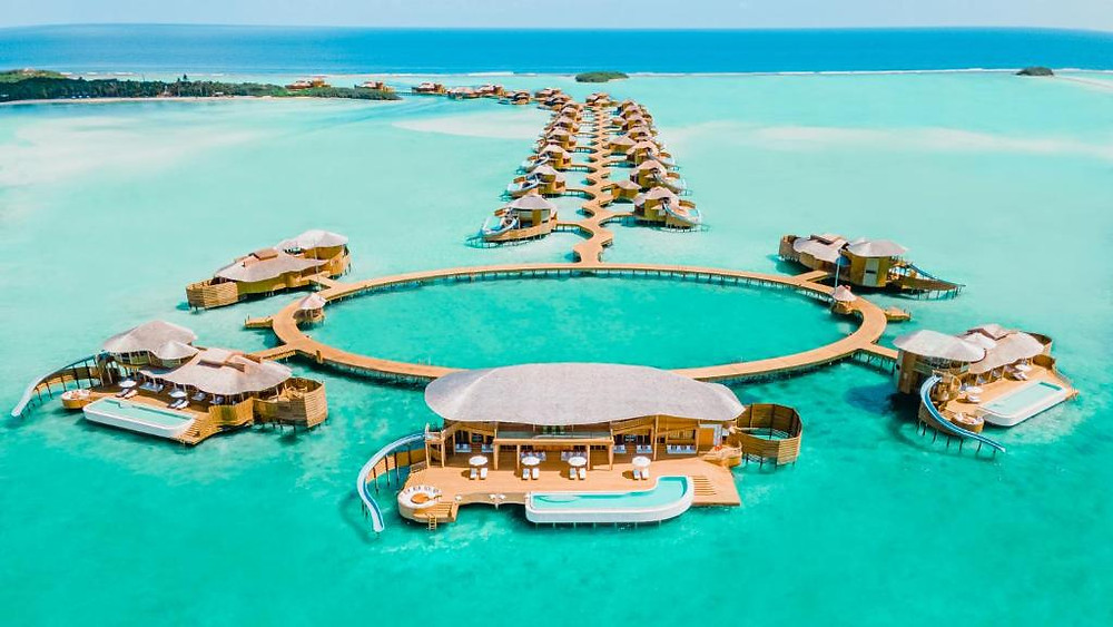 Various ocean villas in the maldives in a circles, all with attached water slides that go into the sea