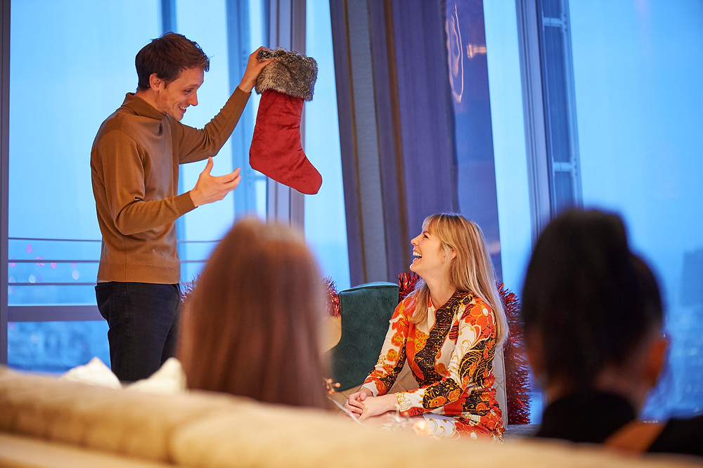 Christmas in the Clouds theatre at the Shangri-La Hotel at the Shard, a man holds up a stocking and a woman laughs