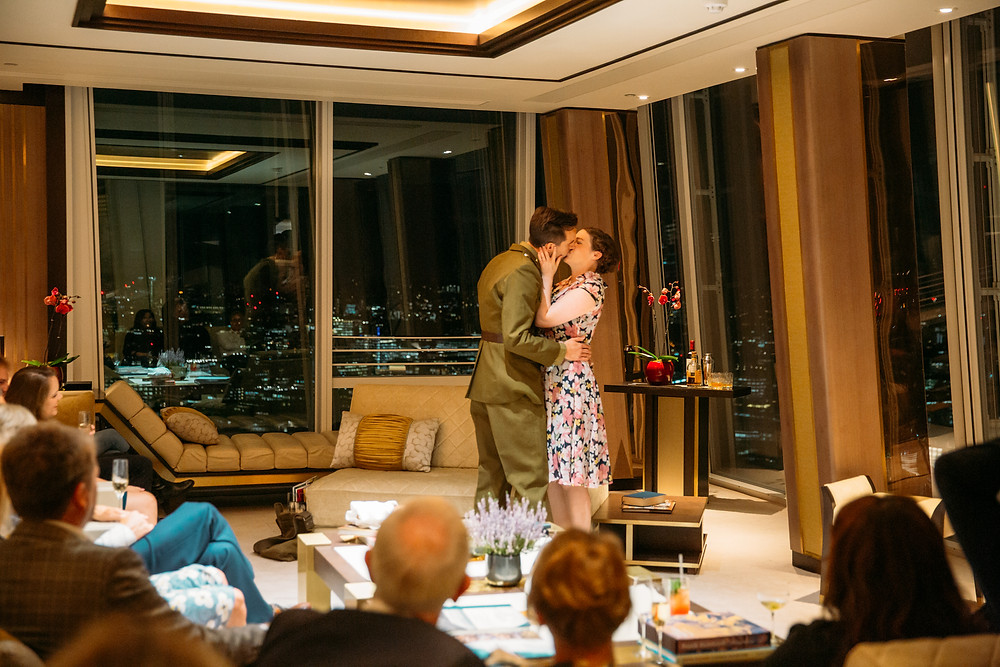 2 actors kissing as Revels in hand performing theatre in the clouds in the shangri-la hotel suite for christmas.