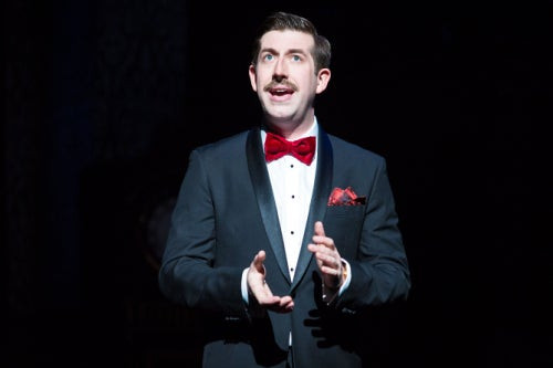 Patrick Warner addressing the audience at the start of The Play That Goes Wrong on the West End