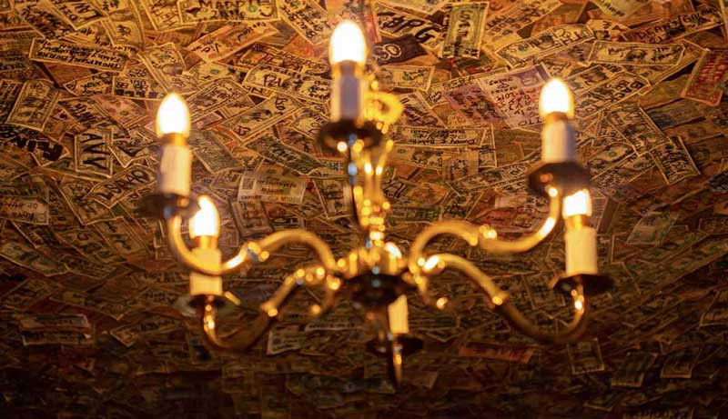 A ceiling covered in dollar bills behind a grand chandelier in haunted London pub the Grenadier