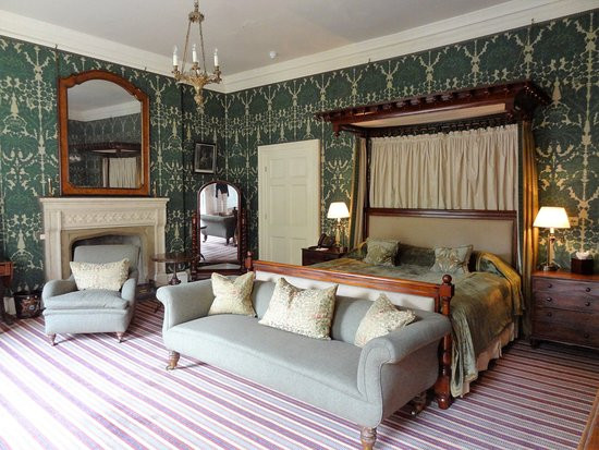 The bedroom at Home House with old fashioned wall paper and grey sofas facing the window where sunlight streams in