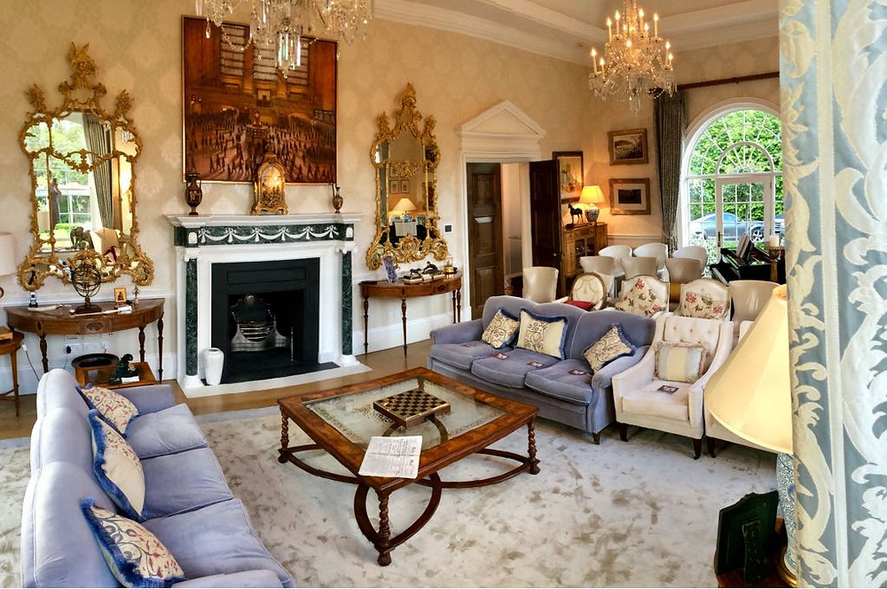 An elegant drawing room with sofas laid out like a theatre auditorium