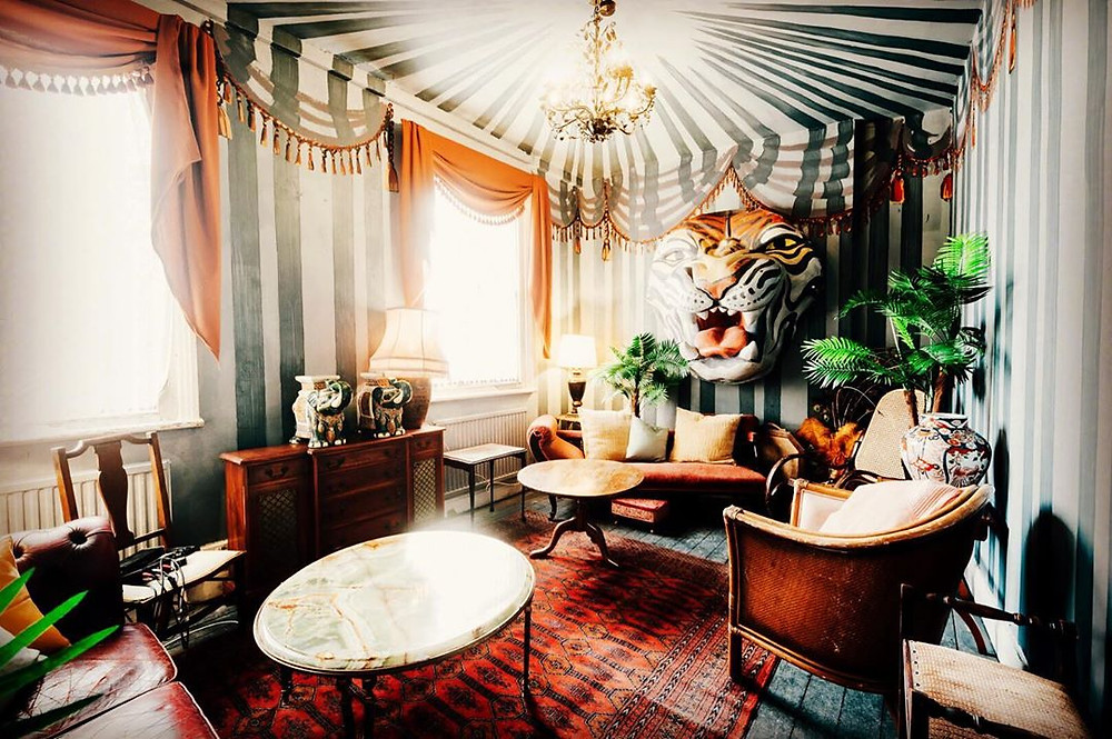 A kooky living room inside a member's club with stripy wallpaper and a large fake tiger's head on the wall