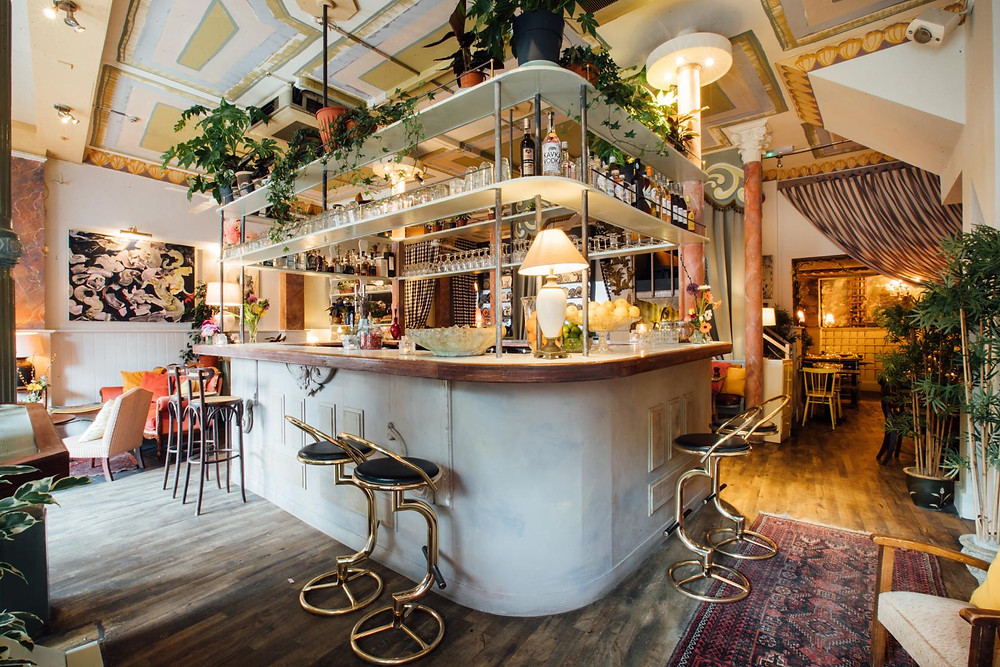 A restaurant bar with gold seating, plants hanging from the ceiling and pastel pink accents