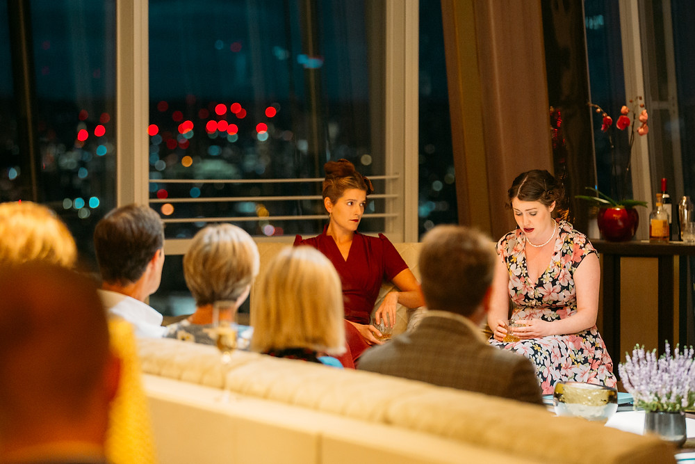 Theatre in the Clouds theatre at the Shangri-La Hotel at the Shard, 2 actresses in 1940s attire are sat on a sofa with an audience watching
