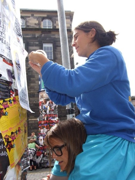 A woman sits on another woman's shoulders to attach posters and flyers to a pillar on the royal mile at the edinburgh fringe festival