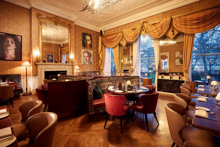 A drawing room in Home house members club in Fitzrovia, with seating and tables and big curtains by the window