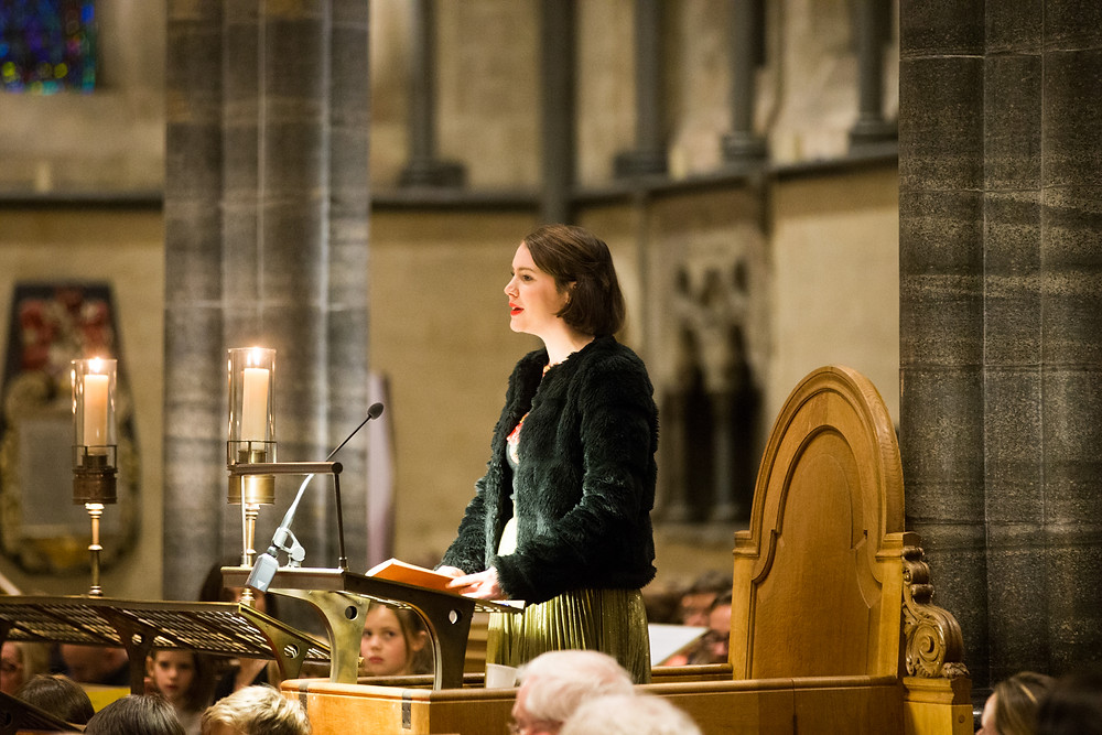 melanie fullbrook an actress stands in a pulpit in a candelit church in a fur jacket reading from a christmas carol