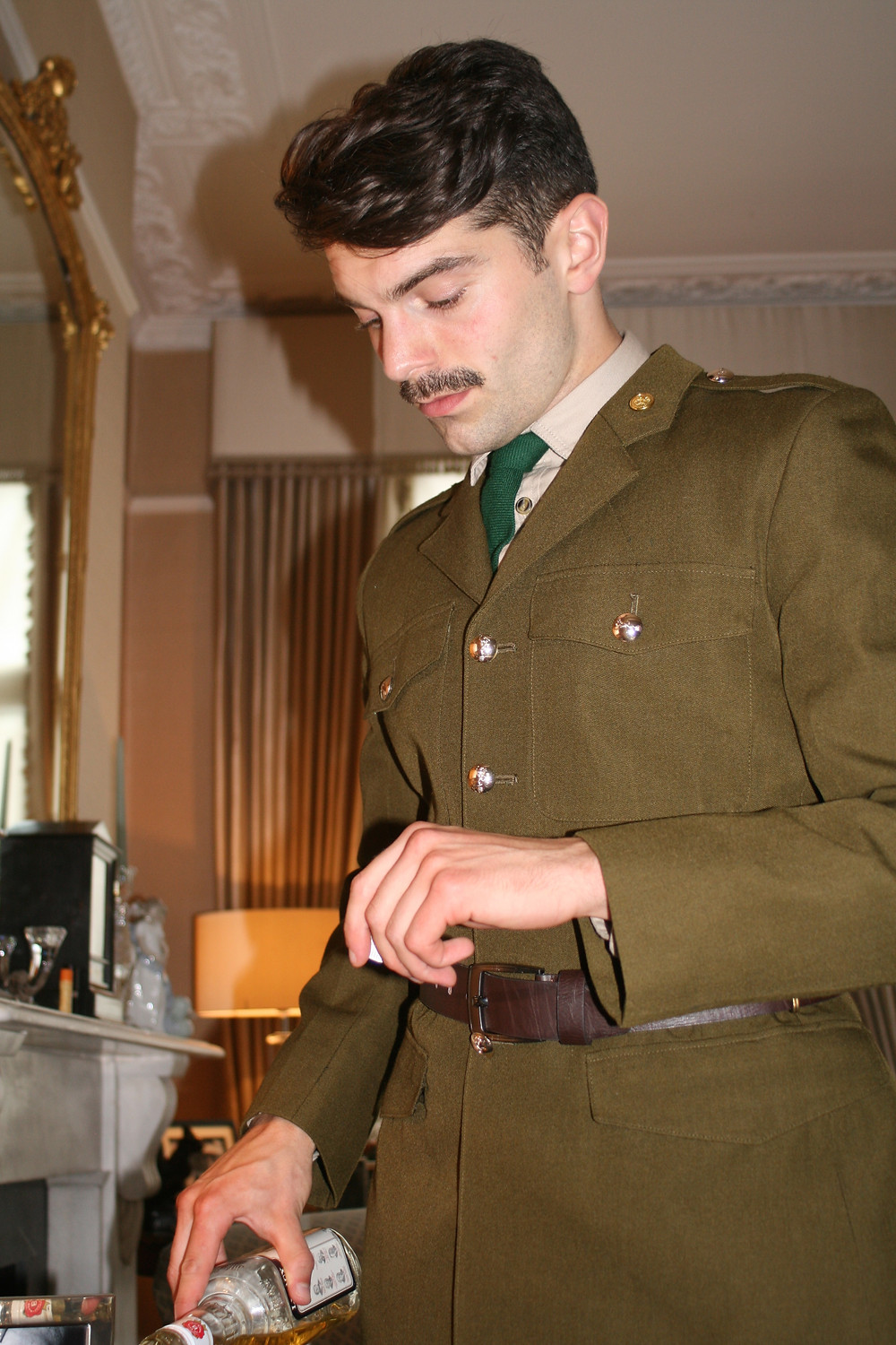 Man in WW2 soldier uniform pouring whisky