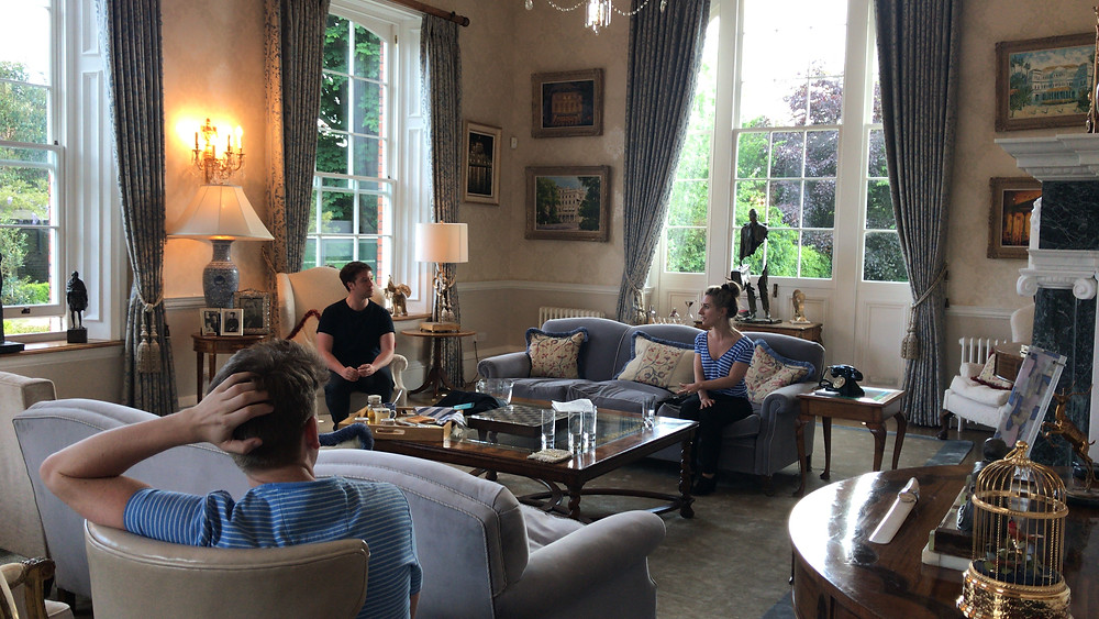 people sit in an elegant and grandiose English drawing room