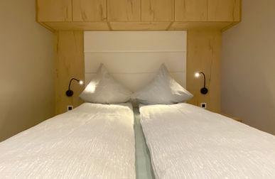Stor dobbeltseng med overskabe og natborde