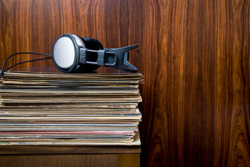stack of vinyl records with dj headphone sitting on top of them