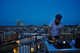 Steely dave dj'ing on a rooftop in barcelona at sunset for brick lane fashion events
