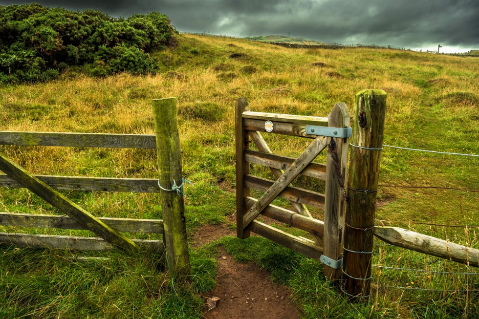 open-wooden-gate-in-fence-with-rocky-tra