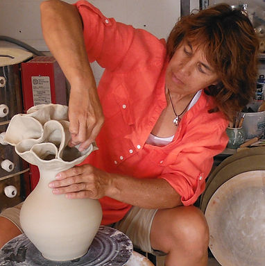 Lee Oululani Plevney throwing a vase on her pottery wheel