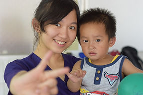 STL volunteer holds a child in her arms and smile at the camera. She holds her pinky and third finger up to a camera while the child mimicks.