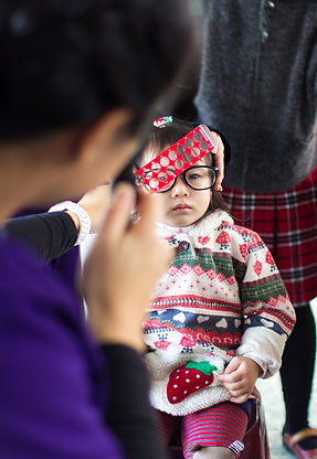 Child in a Christmas sweater and glasss, sits still for an eye exam by an STL voluteer