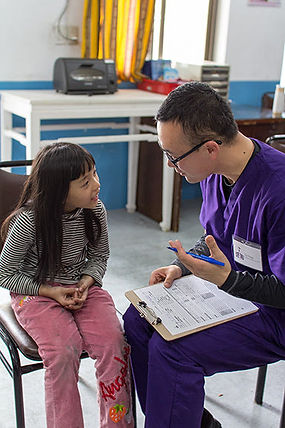 STL volunteer, sitting down on a chair, giving explainations to a young female child