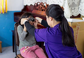 STL founder puts eye exam equipment on a young female child