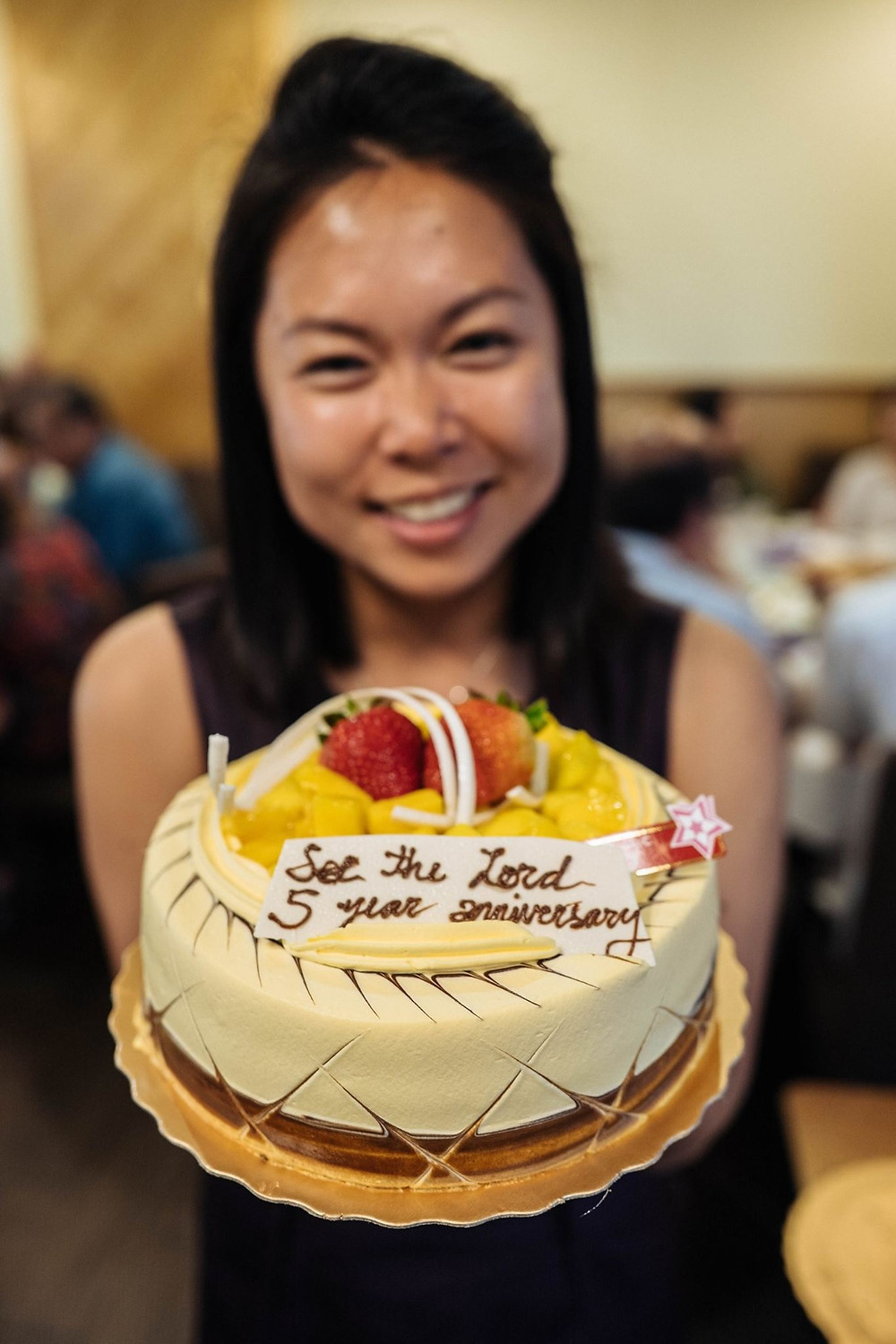 "Kelly Kao holding up a cake with a message saying ""See the Lord 5 Year Anniversary"""