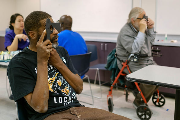 African American patient looks through eye exam equipment