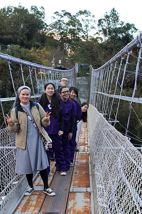 STL volunteers and a nun posing for he camera at a bridge.