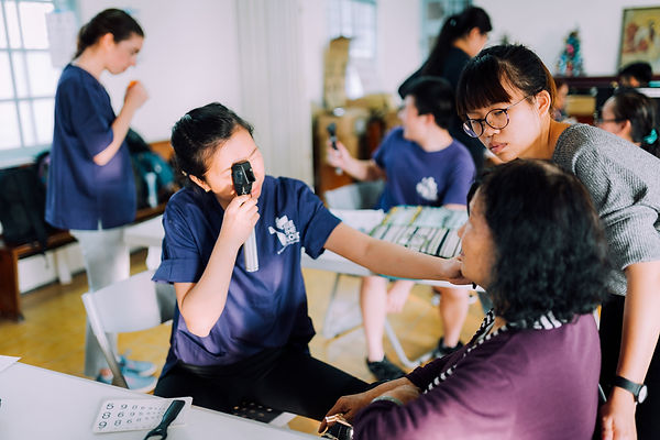 STL volunteer looks through eye scope to examine an Asian patient while another STL voluteer observes